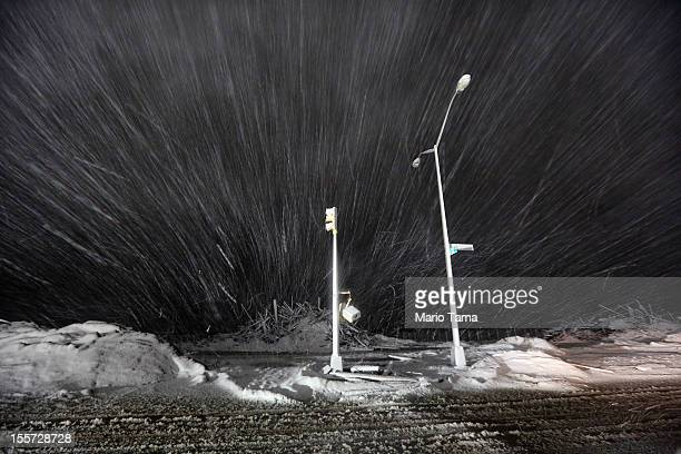 Snow blows past debris and nonfunctioning streetlights during a Nor'Easter snowstorm on November 7 2012 in the Rockaway neighborhood of the Queens...