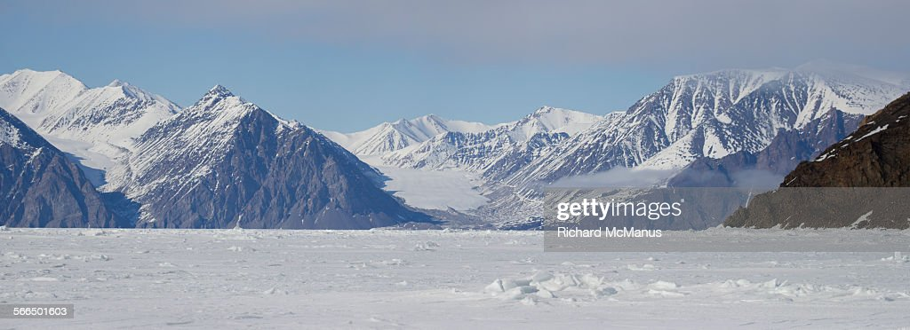 Snow capped mountains over sea ice.