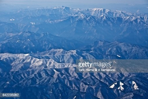 Snow capped Omine mountains aerial view from airplane