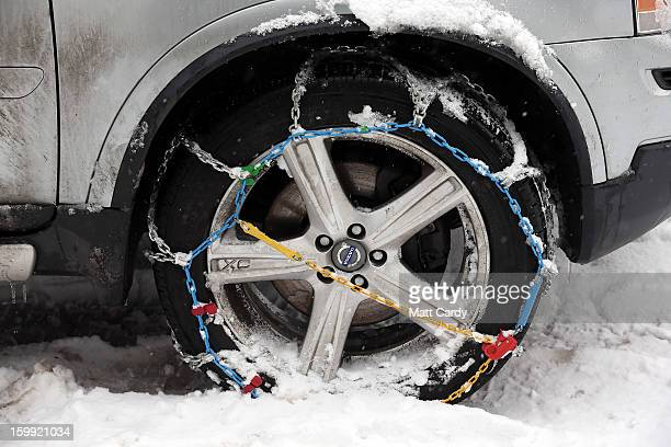 Snow chains are seen attached to the wheel of a 4x4 car in the Mendip village of Priddy on January 23 2013 in Somerset England Parts of the UK...