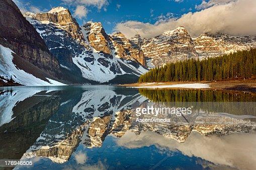 Snow clings to shoreline of mountain lake