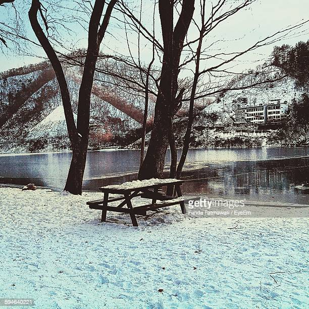 Snow Covered Bench On Field By Lake Against Mountains