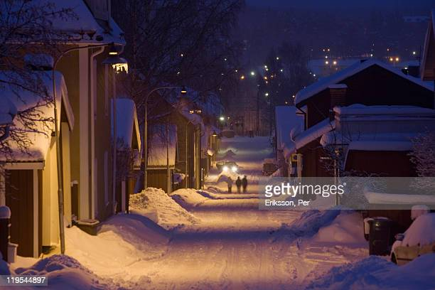 Snow covered buildings and street at dawn