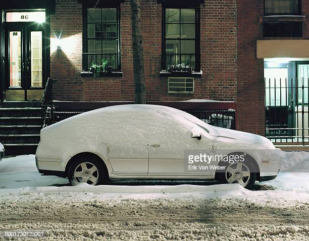 Snow covered car on city street in front of house