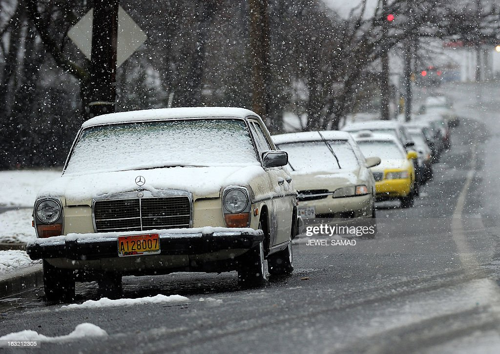 Snow covered cars are seen parked beside a street in Silver Spring, Maryland, on March 6, 2013. A massive winter storm pounding the northern US on March 6, grounded 2,600 flights, closed hundreds of schools and made roadways and highways impassible. At least four people were reportedly killed in accidents on icy and snow covered roads and highways. AFP PHOTO/Jewel Samad
