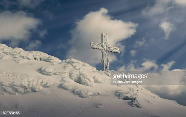 Snow covered cross on a mountain top