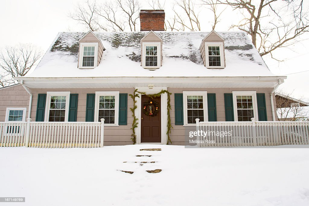 Snow covered Dutch colonial style home