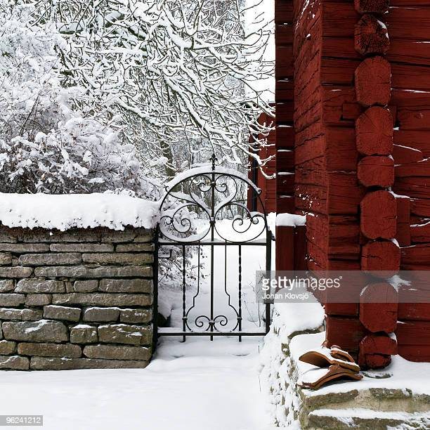 Snow covered garden gate, wall and red barn.