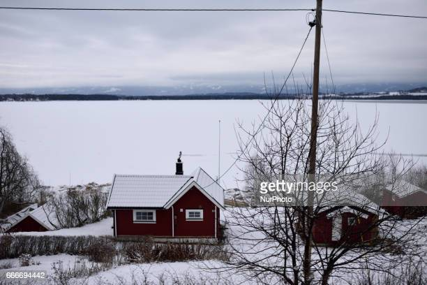 Snow covered houses near a frozen lake along the OsloBergen train route on March 04 2017