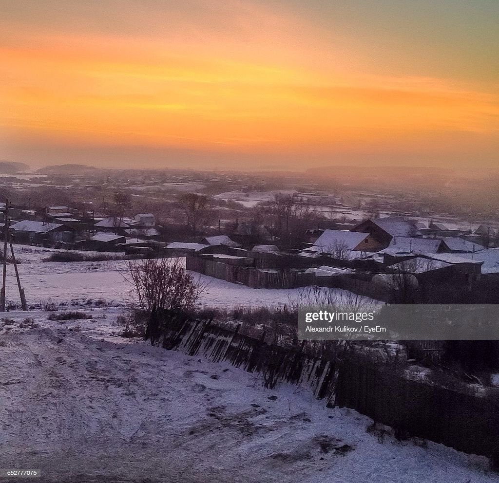 Snow Covered Houses On Field Against Orange Sky In Morning
