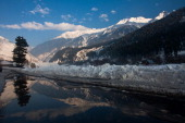 A snow covered mountain is reflected on a puddle in Gagangir 75 km from Srinagar on January 16 2014 east of Srinagar the summer capital of Indian...