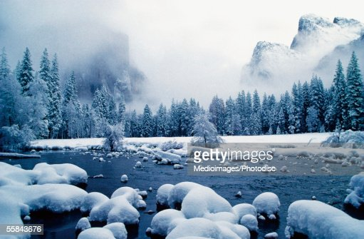 Snow covered mountain peaks and trees, Merced River, Yosemite National Park, Mariposa County, California, USA : Foto de stock