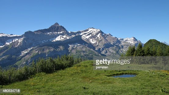 Snow covered mountains and pond near Gstaad : Stock Photo