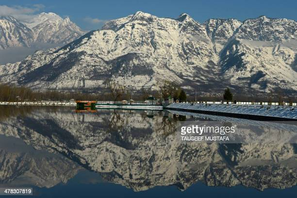 Snow covered mountains are reflected in Dal Lake in Srinagar on March 12 2014 Avalanches triggered by unusually heavy snowfall killed at least six...