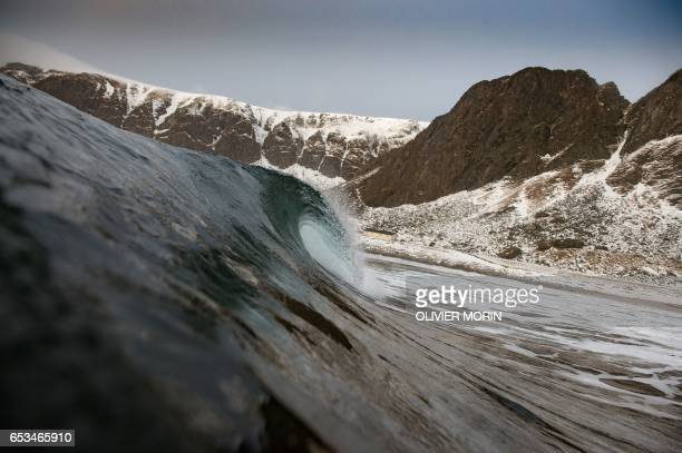 Snow covered mountains are seen from the waters of Unstad along the northern Atlantic Ocean on March 12 where the water temperatures is at five...