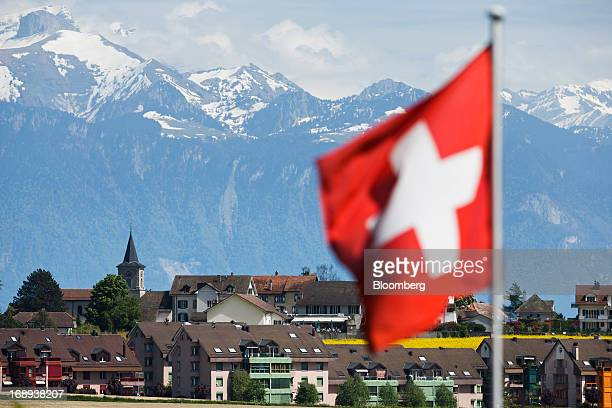 Snow covered mountains stand beyond residential houses and apartment blocks in Ecublens Switzerland on Monday May 13 2013 Risks to Switzerland's...