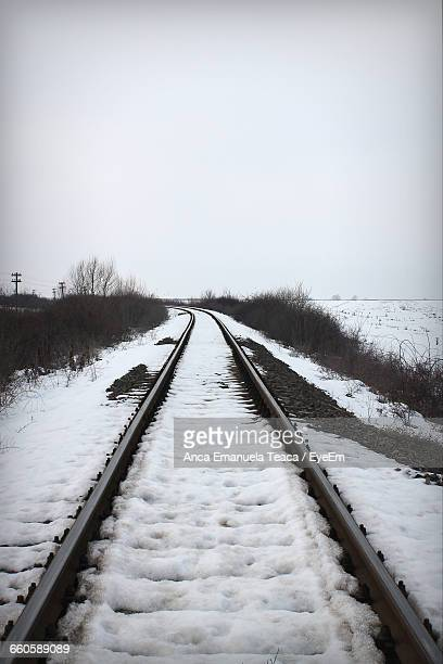 Snow Covered Railroad Tracks Against Clear Sky During Winter