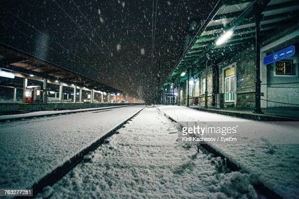 Snow Covered Railroad Tracks At Night