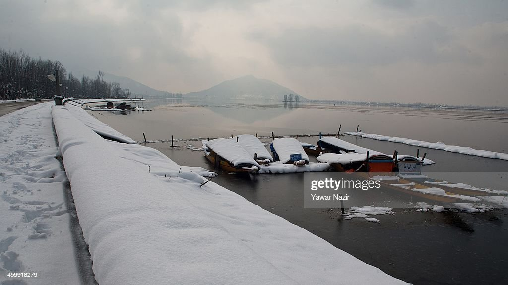 Snow covered Shikara boats are moored to the bank of Dal lake on January 01, 2014 in Srinagar, the summer capital of Indian Administered Kashmir, India. Weather conditions have improved in Kashmir after a spell of heavy snowfall that had distrupted road and air traffic, cutting off the Valley from the rest of world .