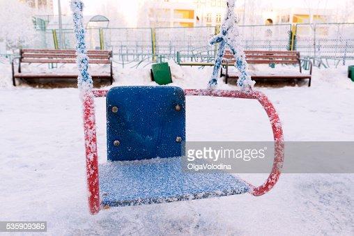 Neve coberta balanço e apresentação de no playground de Inverno : Foto de stock