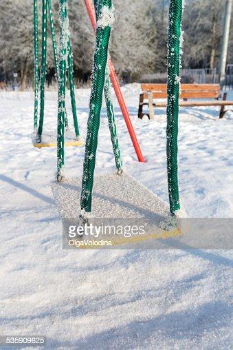 NEVE COPERTO swing e scivolo al parco giochi in inverno : Foto stock