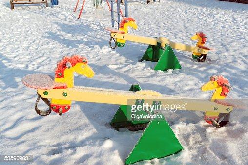 Columpio cubierto de nieve y deslizante en el patio de juegos de invierno : Foto de stock