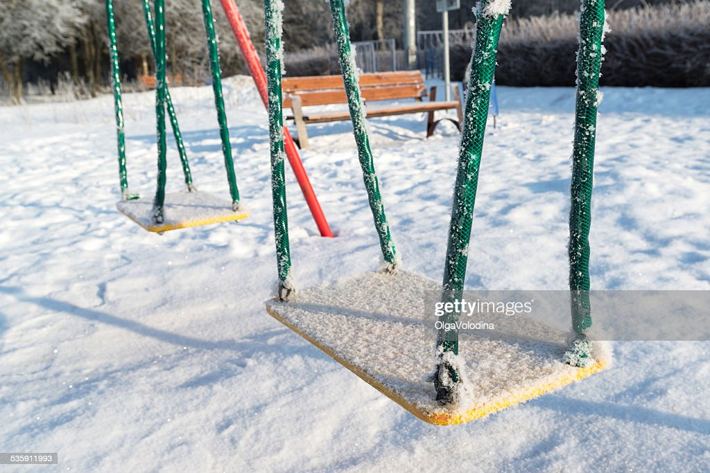 snow covered swing and slide at playground in winter : Stock Photo