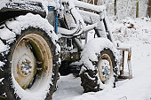 Snow covered tractor in woodland