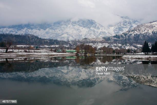 Snow covered Zabarvan mountain range is reflected in a pond on February 07 2014 in Srinagar the summer capital of Indian Administered KashmirIndia...