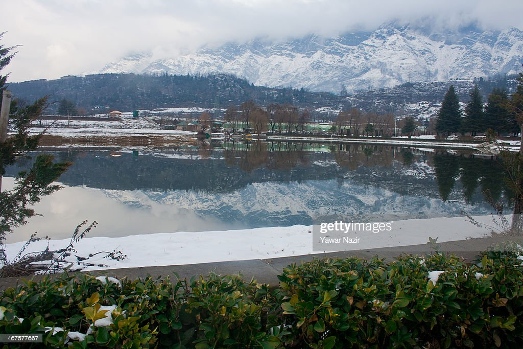 Snow covered Zabarvan mountain range is reflected in a pond on February 07, 2014 in Srinagar, the summer capital of Indian Administered Kashmir,India. Kashmir Valley including the summer capital city of Srinagar, experienced fresh snowfall overnight.