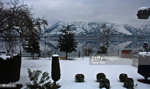 Snow covered Zabarvan mountain range is reflected on the waters of Dal Lake on January 24 2014 in Srinagar the summer capitol of Indian Administered...