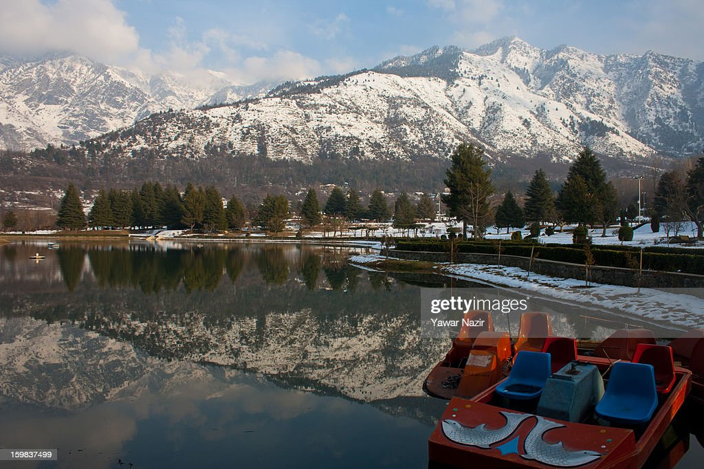 Snow covered Zabarwan mountains are reflected in a pond on January 21, 2012 in Srinagar, the summer capital of Indian Administered Kashmir, India. Weather conditions have improved in Kashmir after a two-day spell of heavy snowfall and rain that had distrupted road and air traffic, cutting off the Valley from the rest of the country.