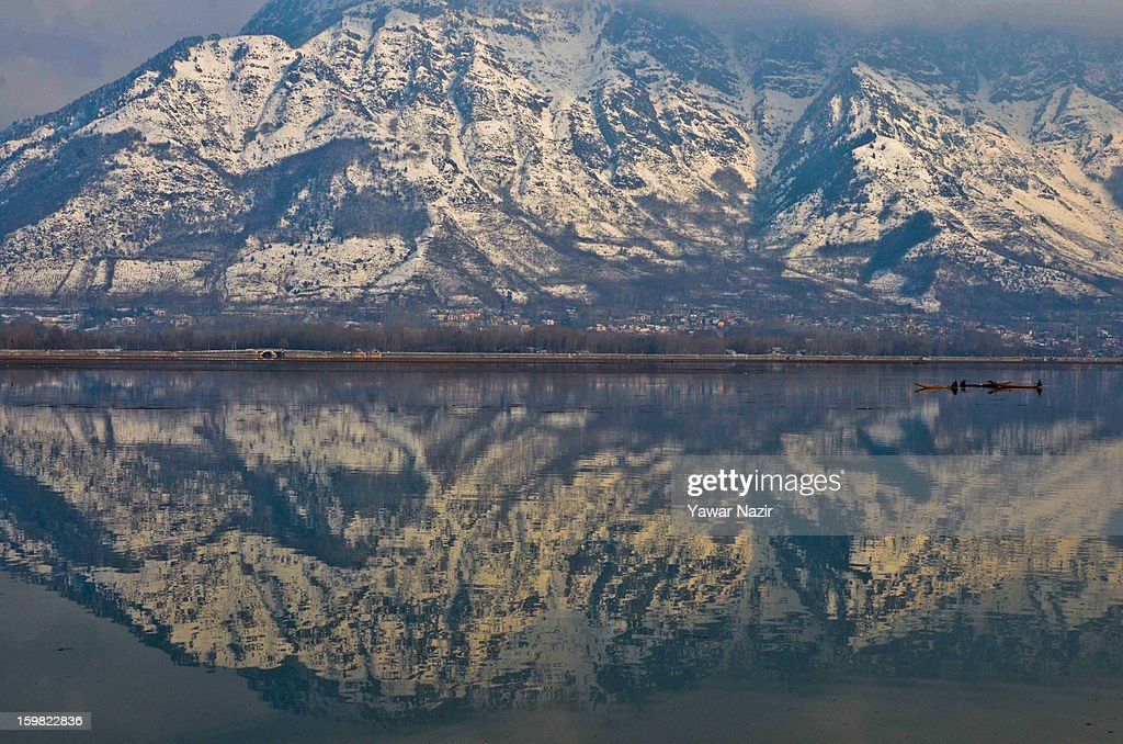Snow covered Zabarwan mountains are reflected on the waters of Dal lake on January 21, 2012 in Srinagar, the summer capital of Indian Administered Kashmir, India. Weather has improved in Kashmir after a two-day spell of snowfall and rains