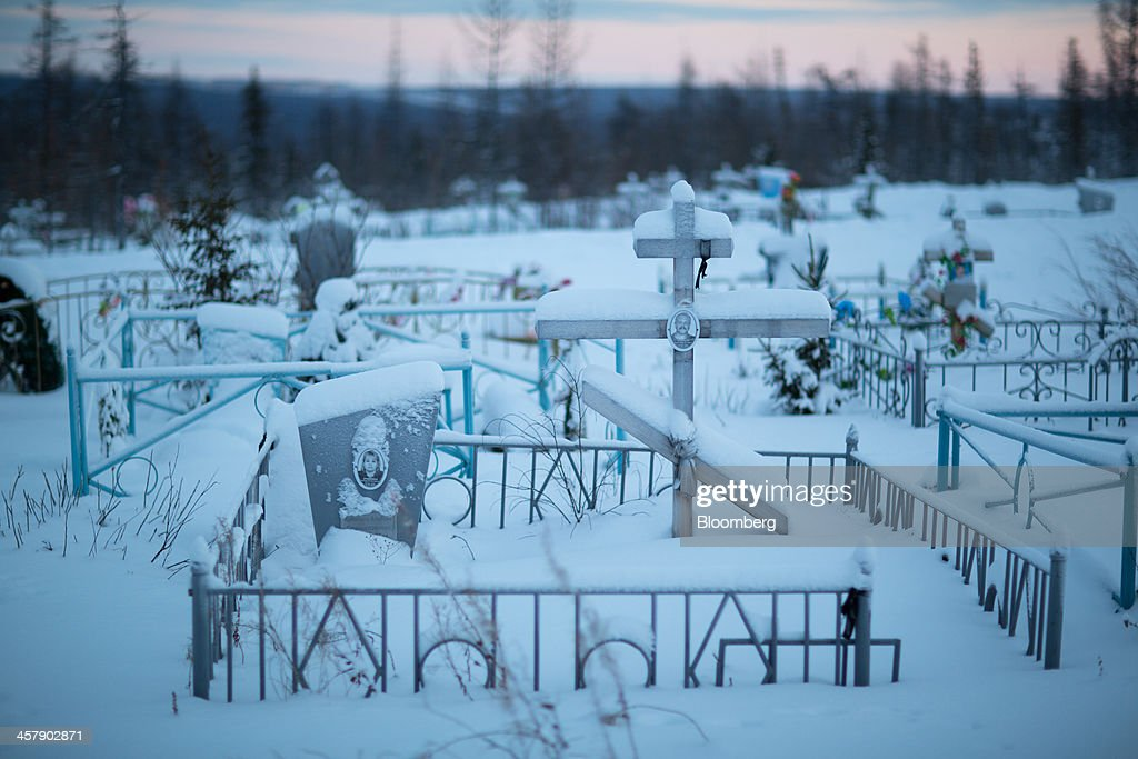 Snow covers burial plots at a city cemetery near the mining town of Udachny, Sakha Republic, Russia, on Monday, Dec. 16, 2013. Russia plans to maintain control of Mirny-based Alrosa, which produces a quarter of the world's diamonds by value and more rough diamonds than De Beers by carat. Photographer: Andrey Rudakov/Bloomberg via Getty Images