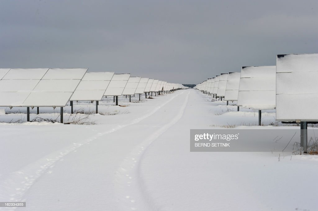 Snow covers solar panels at a solar park in Meuro, northeastern Germany, on February 21, 2013. In spite of the snow layer, the plant situated on an old lignite mine is producing energy. AFP PHOTO / BERND SETTNIK GERMANY OUT