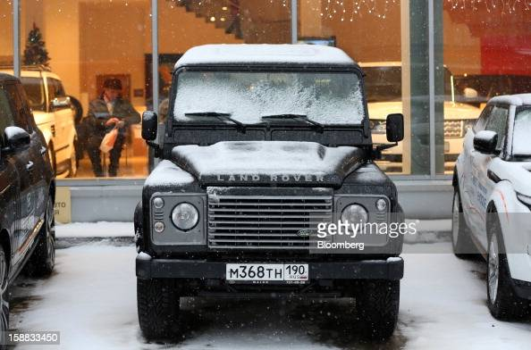 Snow covers the bonnet of a Land Rover Defender customer test automobile outside a Jaguar Land Rover auto dealership in Moscow Russia on Thursday Dec...