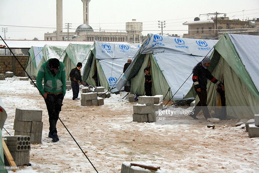 Snow covers the ground outside tents supplied by the United Nations High Commissioner for Refugees (UNHCR) for Syrian refugee families in al-Marj, in the eastern Lebanese Bekaa Valley, on January 9, 2013, as stormy weather sparked widespread flooding, prompting chaos on the roads and a nationwide school closure. The number of Syrian refugees in Lebanon is already totalling 156,000, according to UN figures, and 200,000 according to the Lebanese government estimates. AFP PHOTO /HASSAN JARAH