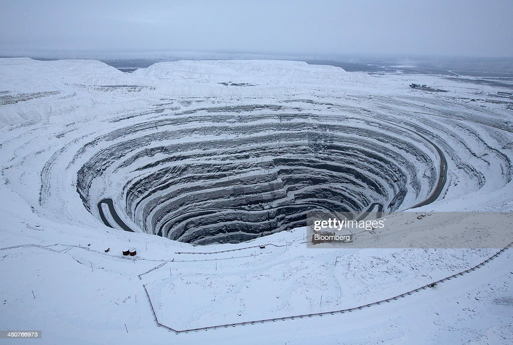 Snow covers the open pit of the Udachny diamond mine operated by OAO Alrosa in Udachny, Russia, on Saturday, Nov. 16, 2013. OAO Alrosa, the world's largest diamond producer, raised about $1.3 billion in an oversubscribed share sale from investors including Oppenheimer Funds Inc. and Lazard Ltd.'s asset-management unit, First Deputy Prime Minister Igor Shuvalov said. Photographer: Andrey Rudakov/Bloomberg via Getty Images