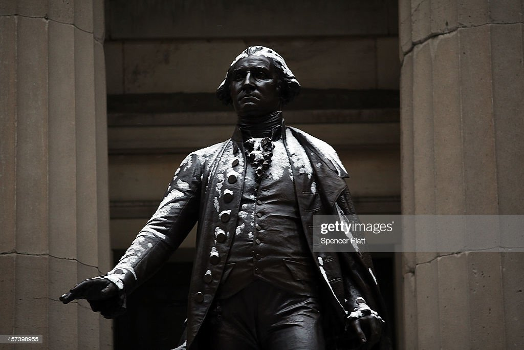 Snow dusts a statue of George Washington along Wall Street during a morning snow storm on December 17 2013 in New York City The metro area is...