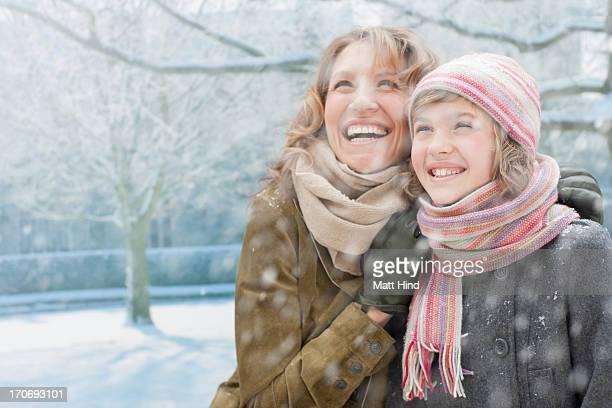 Snow falling on lächelnden Mutter und Tochter
