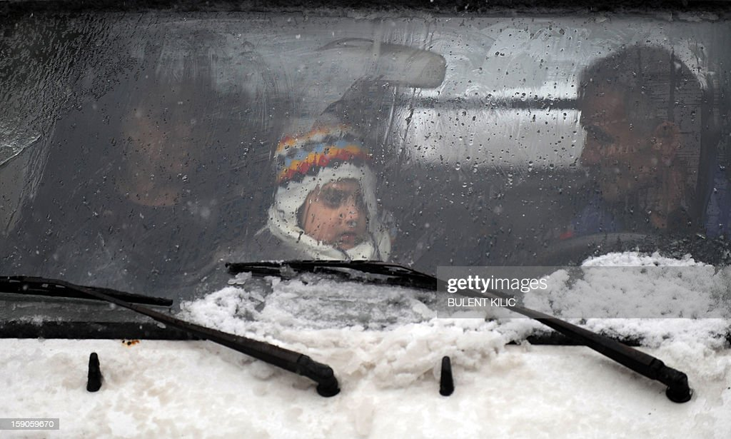 Snow falls as a family wait in a traffic jam in Istanbul, on January 7, 2013. Heavy snowfall blanketed Turkey's commercial hub Istanbul, a city of 15 million, paralysing daily life, disrupting air traffic and land transport. Officials said the snow is expected to continue until late tomorrow, according to the weather forecast.