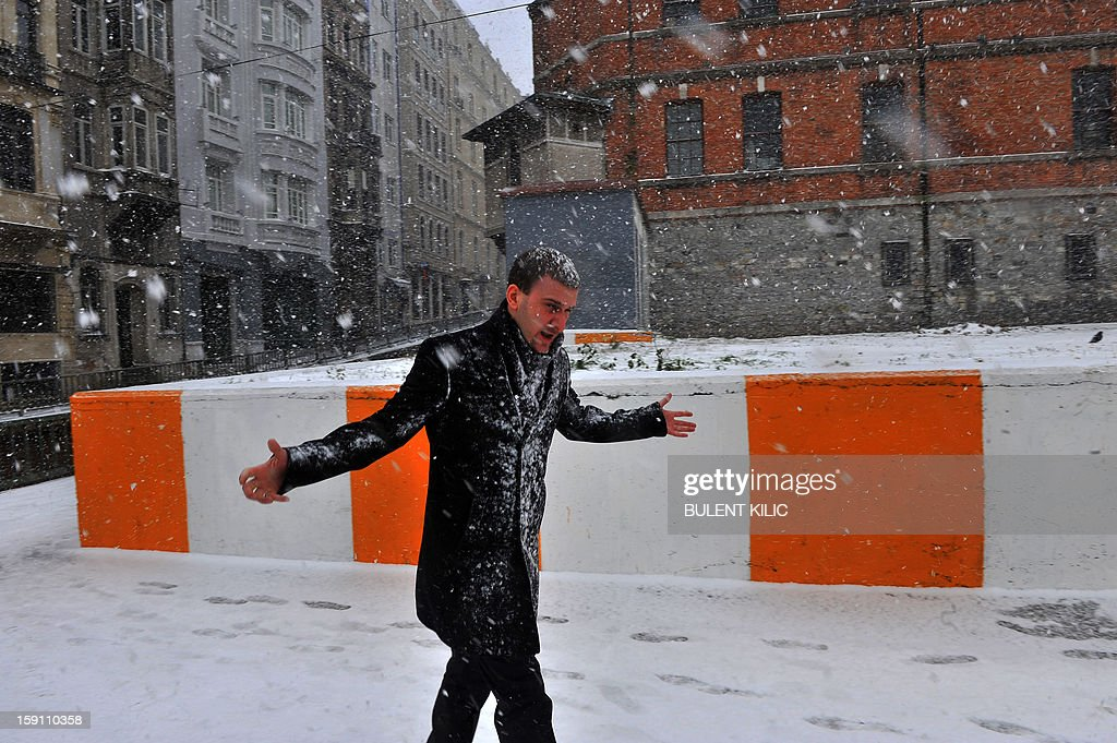 Snow falls as a man walks in Istanbul on January 8, 2013. Heavy snowfall blanketed Turkey's commercial hub Istanbul, a city of 15 million, paralysing daily life, disrupting air traffic and land transport. Officials said the snowis expected to continue until late tomorrow, according to the weather forecast.