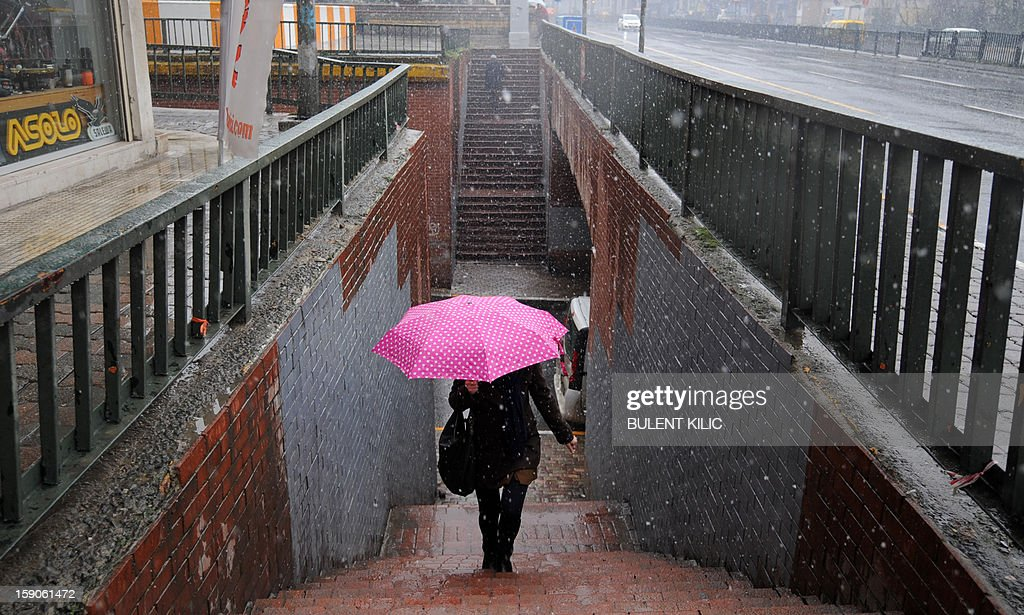 Snow falls as a woman walks with her umbrella in downtown Istanbul on January 7, 2013. Heavy snowfall blanketed Turkey's commercial hub Istanbul, a city of 15 million, paralysing daily life, disrupting air traffic and land transport. Officials said the snow expected to continue until late tomorrow, according to the weather forecast.