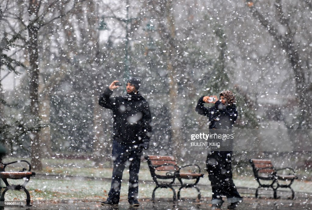 Snow falls as an Arabian tourists take pictures in Istanbul, on January 7, 2013. Heavy snowfall blanketed Turkey's commercial hub Istanbul, a city of 15 million, paralysing daily life, disrupting air traffic and land transport. Officials said the snow is expected to continue until late tomorrow, according to the weather forecast.