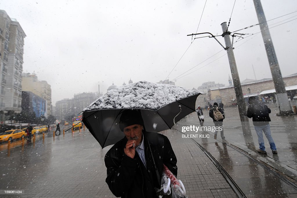 Snow falls as people walk at Taksim square, Istanbul, on January 7, 2013. Heavy snowfall blanketed Turkey's commercial hub Istanbul, a city of 15 million, paralysing daily life, disrupting air traffic and land transport. Officials said the snow is expected to continue until late tomorrow, according to the weather forecast. AFP PHOTO / BULENT KILIC