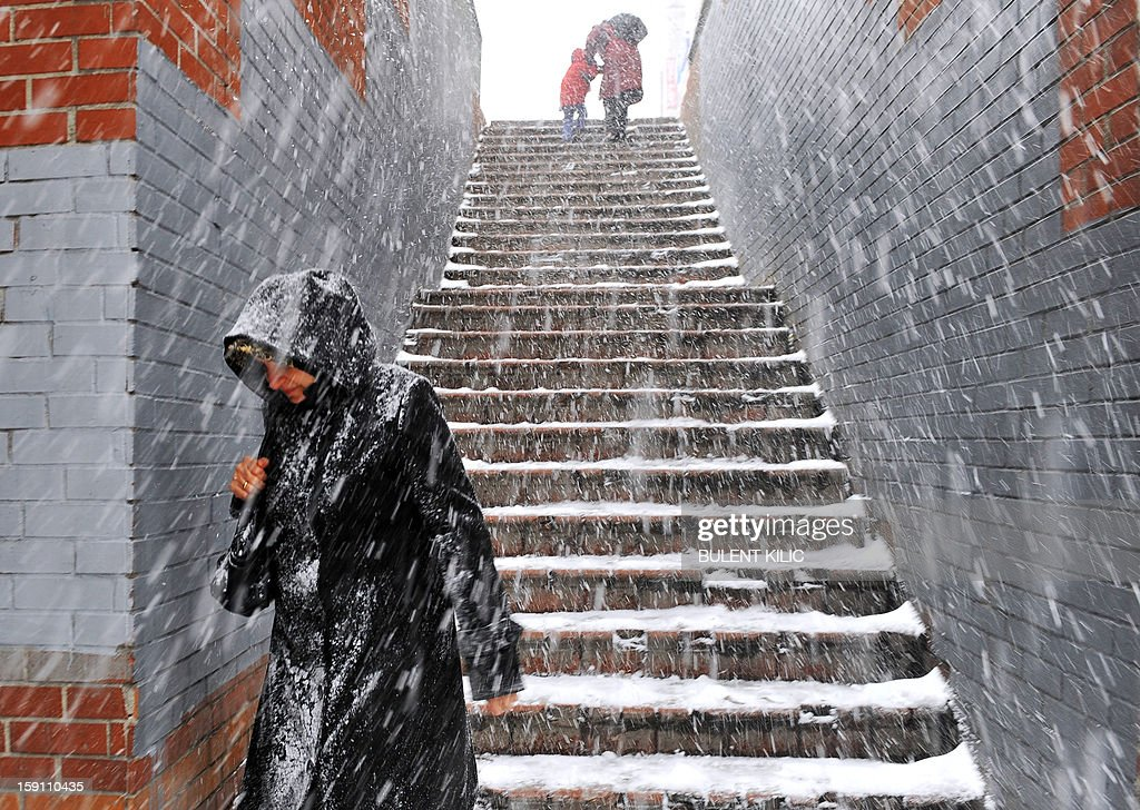 Snow falls as people walk in downtown Istanbul on January 8, 2013. Heavy snowfall blanketed Turkey's commercial hub Istanbul, a city of 15 million, paralysing daily life, disrupting air traffic and land transport. Officials said the snow expected to continue until late tomorrow, according to the weather forecast.
