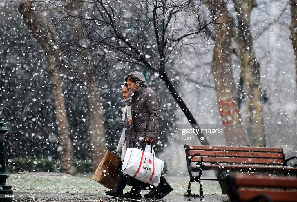 Snow falls as people walk in Istanbul, on January 7, 2013. Heavy snowfall blanketed Turkey's commercial hub Istanbul, a city of 15 million, paralysing daily life, disrupting air traffic and land transport. Officials said the snow is expected to continue until late tomorrow, according to the weather forecast.