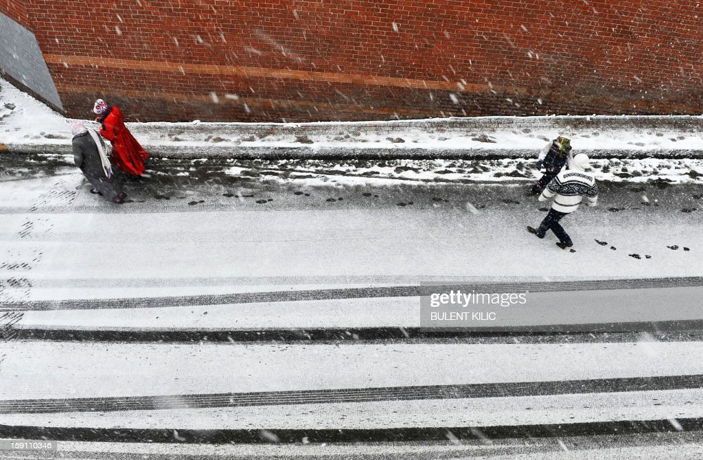 Snow falls as people walk in Istanbul on January 8, 2013. Heavy snowfall blanketed Turkey's commercial hub Istanbul, a city of 15 million, paralysing daily life, disrupting air traffic and land transport. Officials said the snow is expected to continue until late tomorrow, according to the weather forecast.