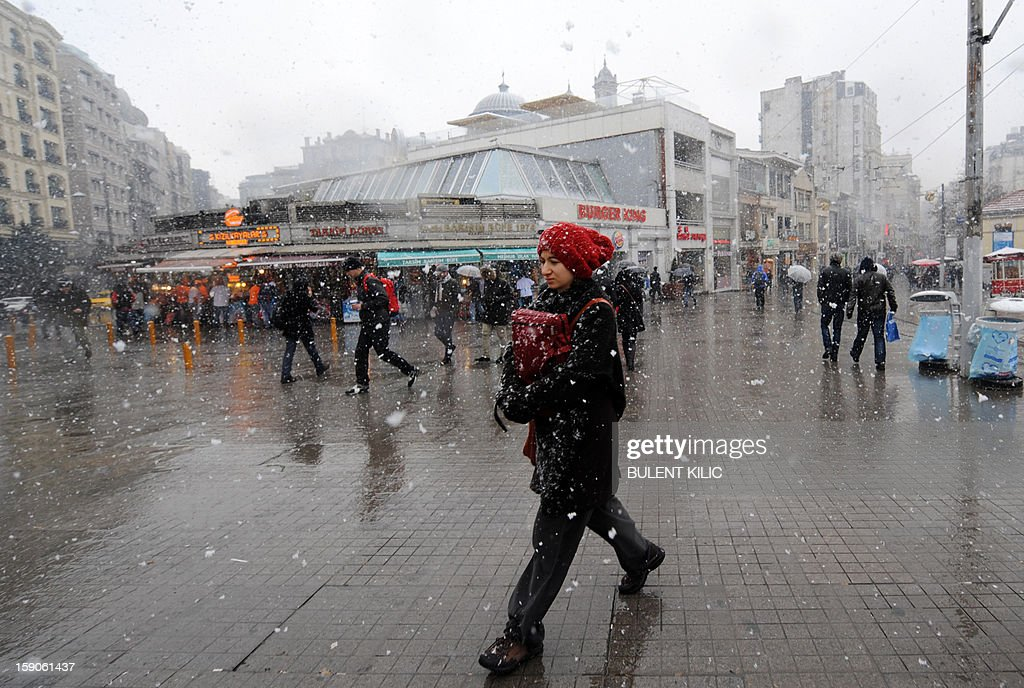 Snow falls as people walk in Taksim square, Istanbul, on January 7, 2013. Heavy snowfall blanketed Turkey's commercial hub Istanbul, a city of 15 million, paralysing daily life, disrupting air traffic and land transport. Officials said the snow is expected to continue until late tomorrow, according to the weather forecast.