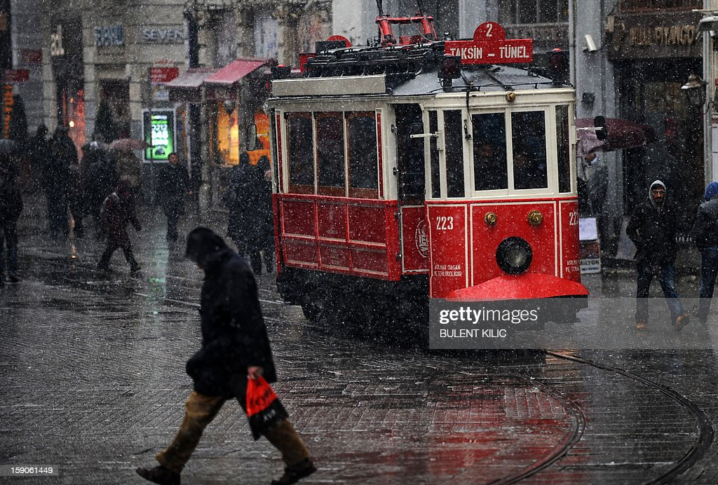 Snow falls as people walk on Istiklal avenue in Istanbul, on January 7, 2013. Heavy snowfall blanketed Turkey's commercial hub Istanbul, a city of 15 million, paralysing daily life, disrupting air traffic and land transport. Officials said the snow is expected to continue until late tomorrow, according to the weather forecast. AFP PHOTO / BULENT KILIC